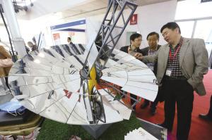3月29日,为期3天的2016中国国际清洁能源博览会在中国国际展览中心开幕,全面聚焦各种清洁能源发电及相关技术,特别包括太阳能光伏、太阳能光热、风能、生物质能、天然气等新能源和可再生能源发电技术与电网接入技术及设备、储能、充电设施等方面的新技术、新产品。 图为当日在北京冬奥张家口绿色能源展台,观众看1:10比例的光电转化率最高的蝶式斯特林光热发电模型燃气发电机组模型。(云 珠)